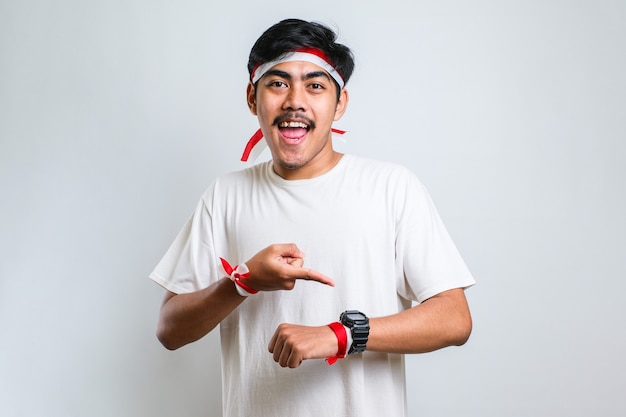Handsome asian an wearing casual clothes looking at the watch time worried, afraid of getting late over white background