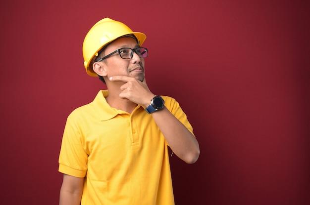黄色の背景に対してあごに手を考えてヘルメットをかぶってハンサムなアジアの労働者の男。