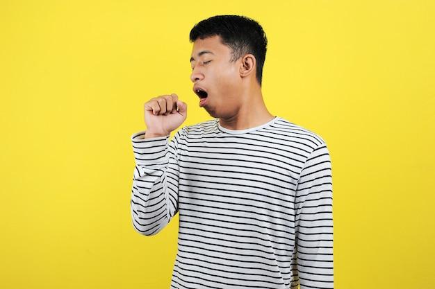 잘생긴 아시아 청년은 감기나 기관지염의 증상으로 몸이 좋지 않고 기침을 합니다. 노란색 배경에 고립 된 의료 개념