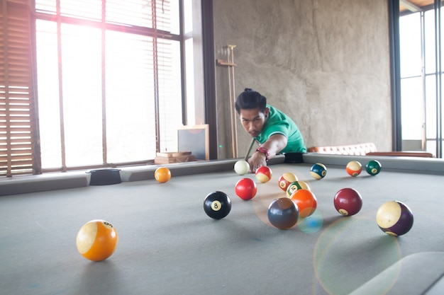 Handsome asian young man playing pool at home, selective focus on ball