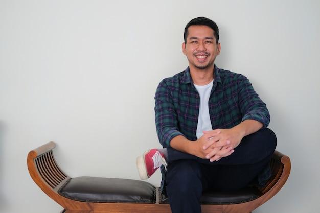 Красивый азиатский молодой человек сидит на деревянном диване, дружелюбно улыбаясь