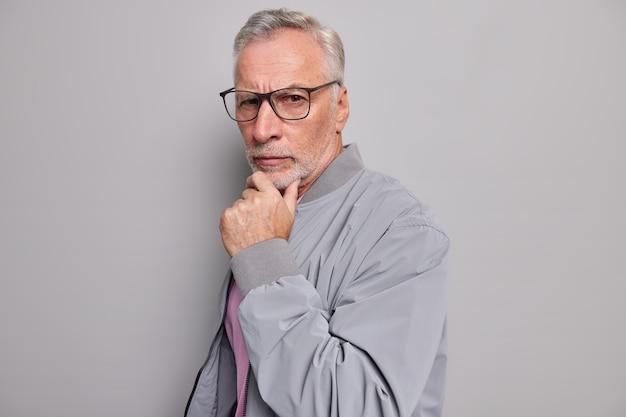 Handsome assertive elderly man stands sideways holds hand on chin