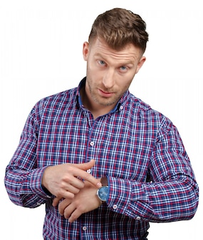 Handsome astonished young business man pointing on watch