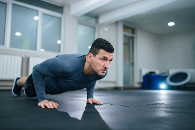 Handsome athlete doing push-ups indoors. low angle image.