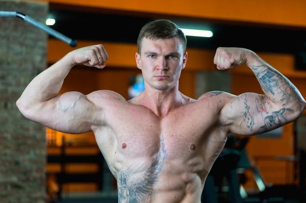 ジムのハンサムなアスリートは、ポンプで汲み上げられた筋肉を示しています。スポーツライフスタイル。
