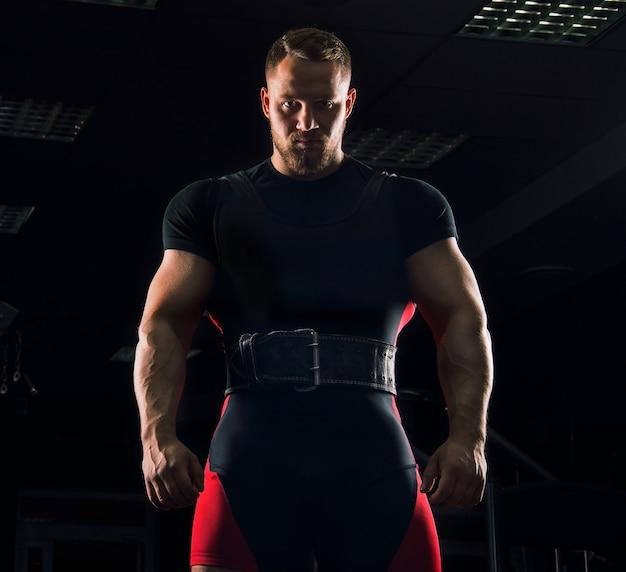 Красивый спортсмен стоит со спортивным поясом в тренажерном зале