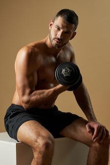 Красивый спортсмен в черных шортах начинает тренировку в тренажерном зале с гирями, изолированными на