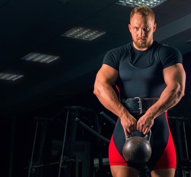 Красивый спортсмен стоит с гирькой в руках в тренажерном зале