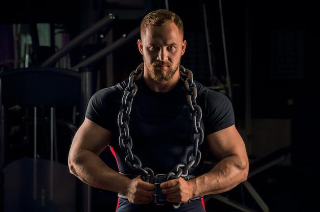 Красивый спортсмен с цепочкой на шее стоит в спортзале и смотрит прямо перед собой