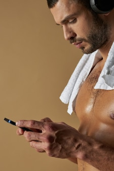 Handsome athlete with muscular body typing message on cell phone
