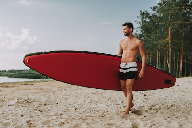Handsome athletic guy with surf standing on beach.