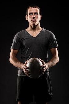Красивый спортивный мужской игрок в регби, держащий мяч