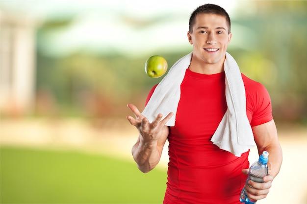 ジムで首にタオルでハンサムな運動選手
