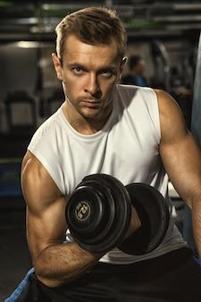 自信を持ってジムでダンベルでワークアウトカメラを探しているハンサムなアスレチック筋肉男