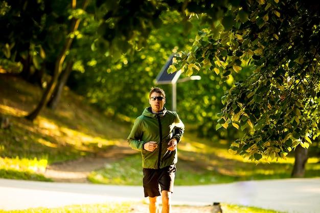 日当たりの良い緑豊かな公園でトレーニングをしながら走っているハンサムな運動青年