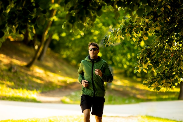 Handsome athletic young man running while doing workout in sunny green park