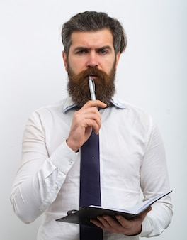 Handsome attractive business man having raised pen and notebook in hands, isolated on white background.
