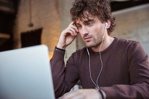 Handsome attractive concentrated serious curly guy in brown sweetshirt working with laptop and using eraphones