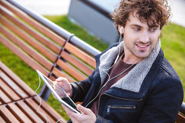 Handsome attractive curly young man in black jacket sitting on wooden bench in the park and listening to music from tablet