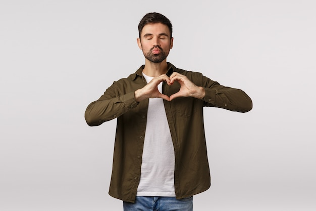 Handsome attractive and cute young gay man with beard in modern outfit, close eyes and pull lips, pouting to kiss, make heart gesture, express affection, love partner, standing white background