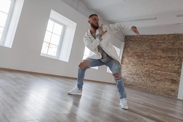 댄스 스튜디오에서 춤을 찢어 청바지와 유행의 옷을 입고 잘 생긴 매력적인 댄서 남자