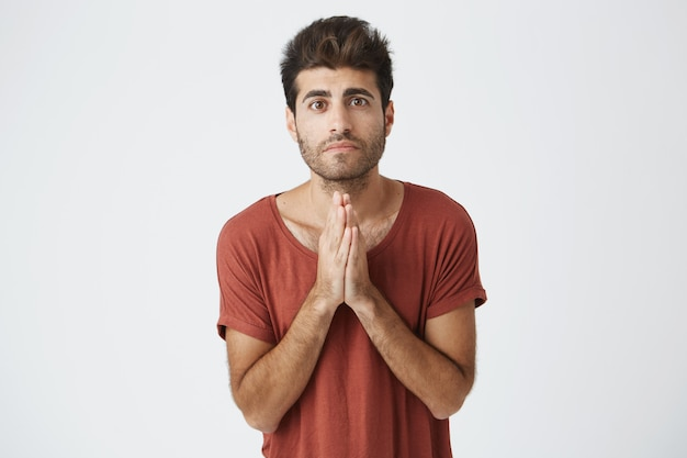 Handsome attractive disappointed guy pledging for something. man holding hands in prayer hoping for fortune. sad boy telling sorry and making promises to his girlfriend