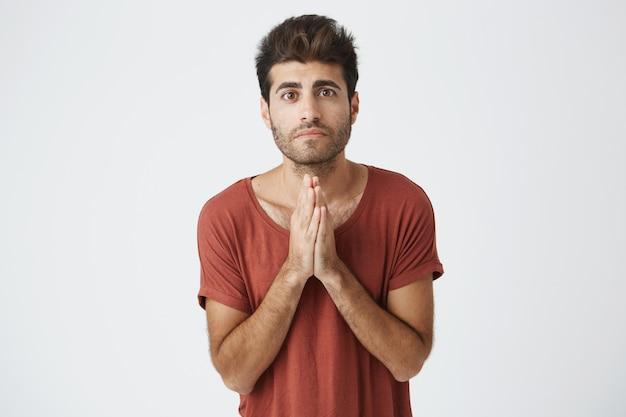 Bel ragazzo deluso attraente impegnandosi per qualcosa. uomo che si tiene per mano nella preghiera sperando in fortuna. ragazzo triste che dice scusa e fa promesse alla sua ragazza