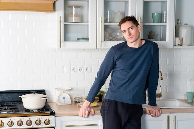 Красивый привлекательный парень, молодой серьезный мужчина позирует, стоя дома на кухне возле плиты утром