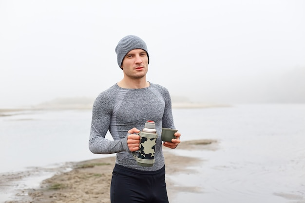 Handsome attractive man on bank of river, posing with thermos near beautiful foggy lake, front view of pensive man enjoying hot coffee or tea, wearing cap