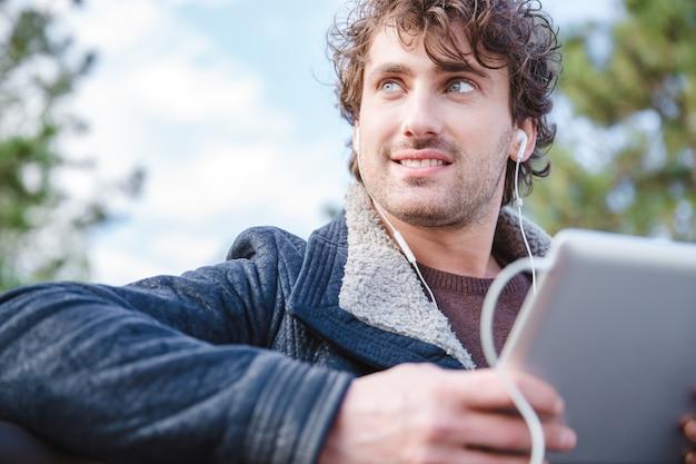 태블릿을 사용하고 멀리보고 검은 재킷에 잘 생긴 매력적인 웃는 행복 즐거운 젊은 남성