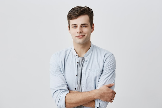 Handsome attractive young european man in casual shirt with dark hair and blue eyes, keeping arms folded, confidently looking  with pleasant smile. face expression