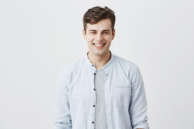 Handsome attractive young man dressed in light blue shirt over t-shirt with dark hair and appealing blue eyes looknig , smiling broadly, demonstrating white teeth, being happy and pleased.