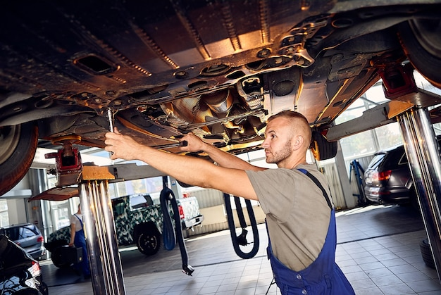 Handsome auto mechanic checking running gear of automobile on service station