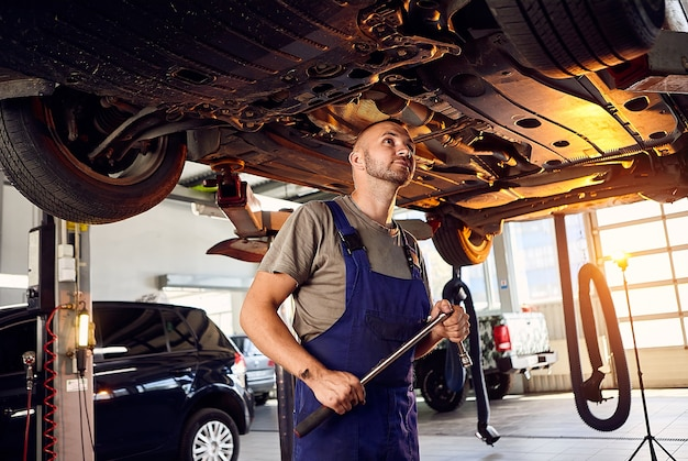 Handsome auto mechanic checking running gear of automobile on service station.