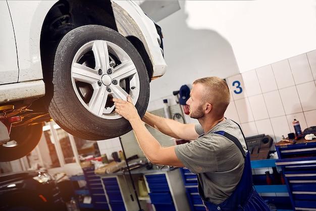 잘 생긴 자동차 정비사가 차에 바퀴를 설치하고 검사합니다.