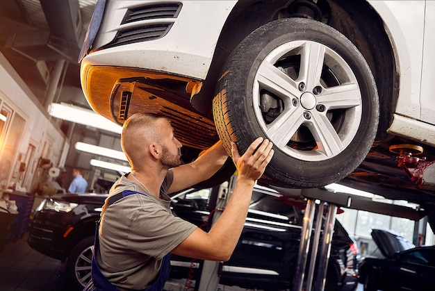 Handsome auto mechanic installs and inspects the wheels on the car