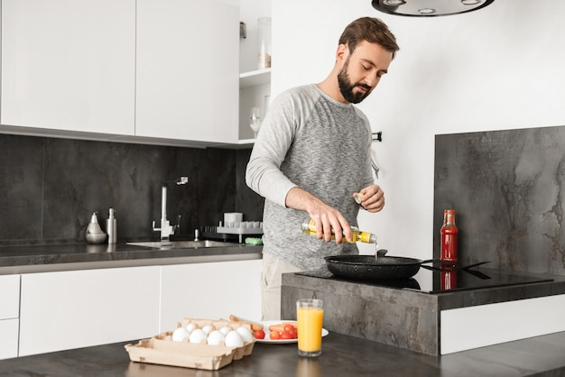 Handsome bachelor with short brown hair and beard cooking omelet with vegetables in home kitchen, using frying pan