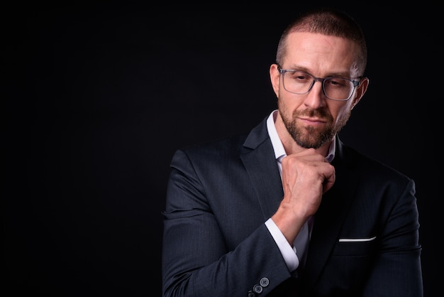 黒いスペースに対して眼鏡をかけているスーツのハンサムなハゲひげを生やしたビジネスマン