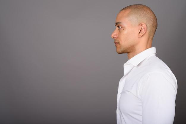 Handsome bald businessman wearing white shirt on gray