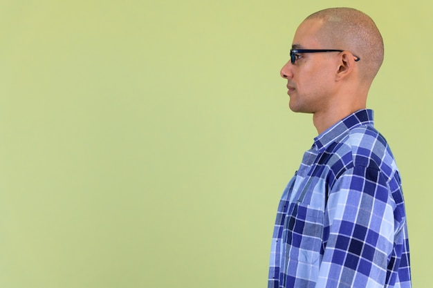 Handsome bald hipster man with mixed race against colored wall