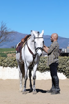Handsome bald male leading his white horse .