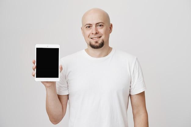 Uomo calvo bello che mostra lo schermo della compressa digitale