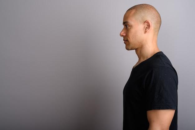 Handsome bald man wearing black shirt on gray