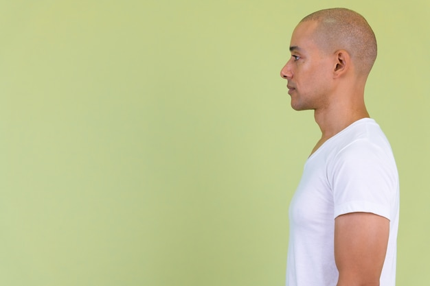 Handsome bald man with mixed race against colored wall