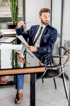 고급 사무실 내부에 앉아 노트북으로 일하는 잘생긴 은행원. 전체 길이 초상화