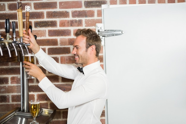 Handsome bar tender pouring a pint