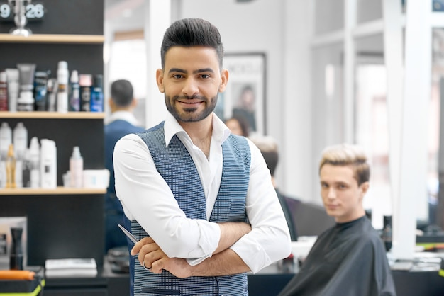 Handsome barber posing standing in front of young client sitting near mirror.