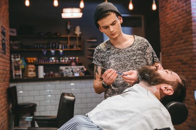 Красивый парикмахер бреет бородатого мужчину опасной бритвой в парикмахерской