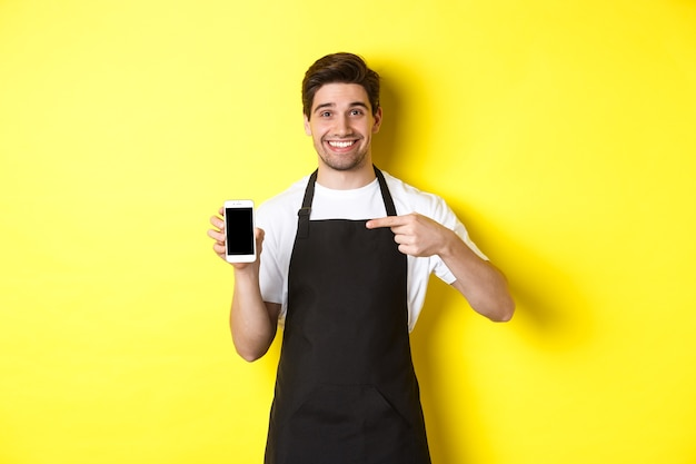 Handsome barista in black apron pointing finger at mobile screen, showing app and smiling, standing over yellow background.