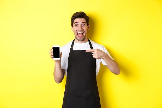 黄色の背景の上に立って、アプリを表示し、笑顔で、モバイル画面で指を指している黒いエプロンのハンサムなバリスタ。
